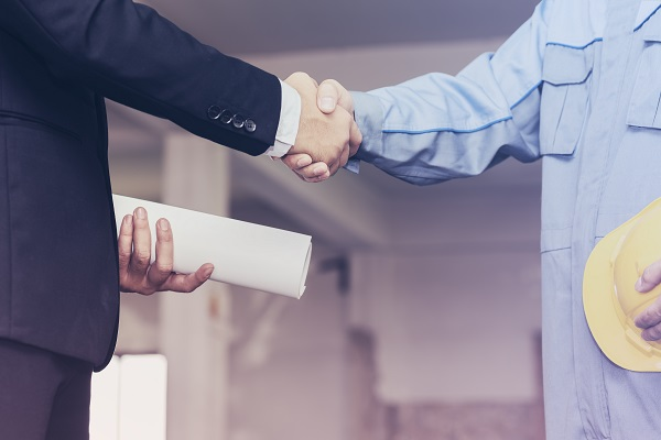 Architect engineer shaking hands with businessman on site
